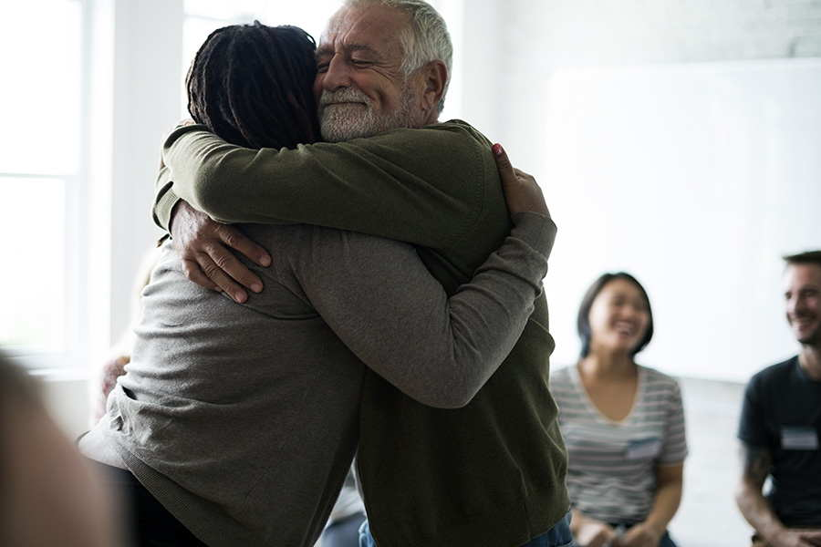 Two people hugging at an addiction support group meeting